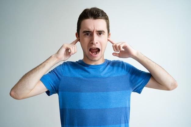 Hombre molesto gritando y parando orejas con dedos