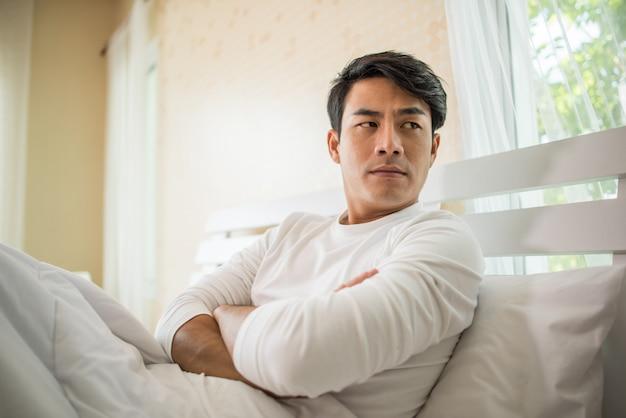 Hombre molesto que tiene problemas para sentarse en la cama después de discutir con su novia