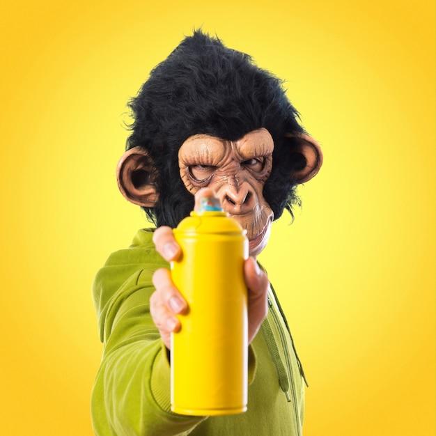 Hombre del mono con el aerosol en fondo colorido