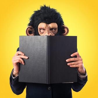 Hombre del mono que oculta detrás de un libro en fondo colorido