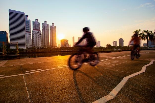 Hombre montando bicicleta en carril bici en el parque público de la ciudad en la mañana