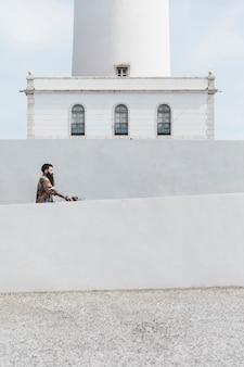 Hombre montando la bicicleta cerca del faro blanco