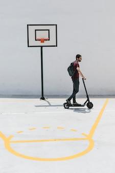 Hombre montando e-scooter en una cancha de baloncesto