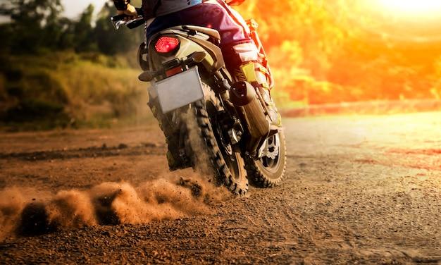 Hombre montando motocicleta de gira deportiva en el campo de tierra