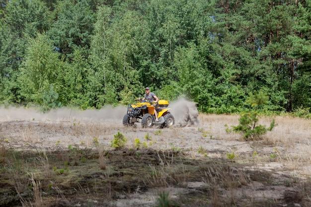 Hombre montando un quad amarillo atv todo terreno vehículo en un bosque de arena. movimiento de deporte extremo, aventura, atracción turística.