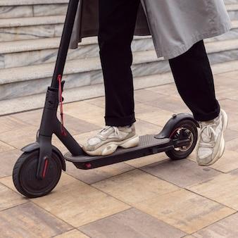 Hombre montando su scooter eléctrico en la ciudad