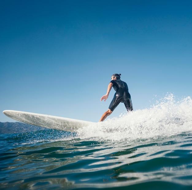 Hombre montando su vista lateral de la tabla de surf