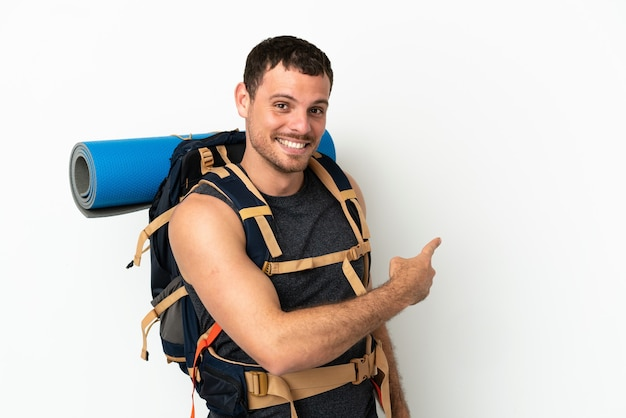 Hombre montañero brasileño con una gran mochila sobre fondo blanco aislado apuntando hacia atrás