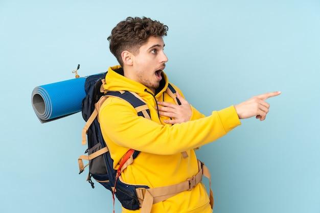 Hombre montañero con una mochila grande apuntando con el dedo hacia el lado