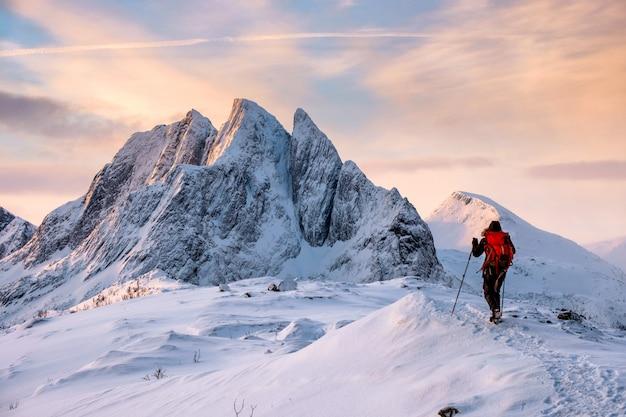 Hombre montañero sube en la cima de la montaña nevada