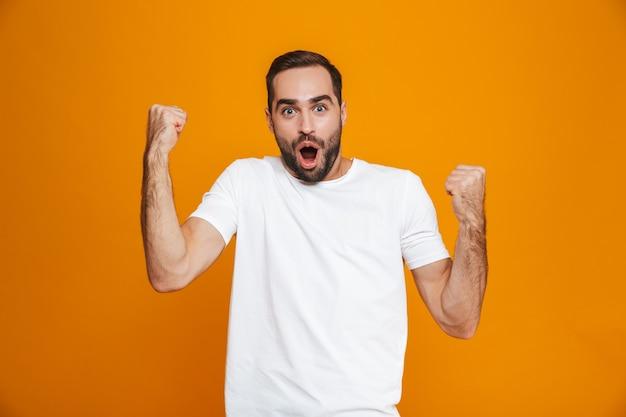 Hombre morena con barba y bigote apretando los puños de alegría mientras está de pie, aislado en amarillo