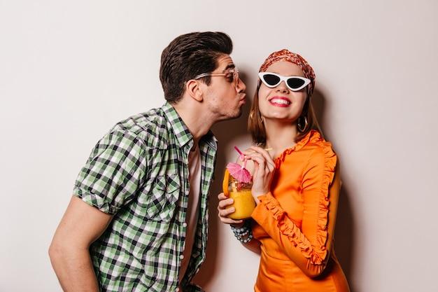 Hombre morena en camisa a cuadros besa a su novia. señora con gafas y vestido naranja está sonriendo y sosteniendo un cóctel.