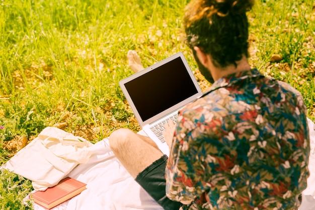 Hombre morena joven que mantiene el ordenador portátil en prado