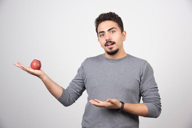 Hombre morena con manzana roja mirando a cámara.