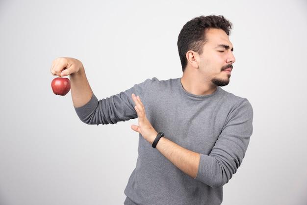 Hombre morena rechazando manzana roja sobre gris.