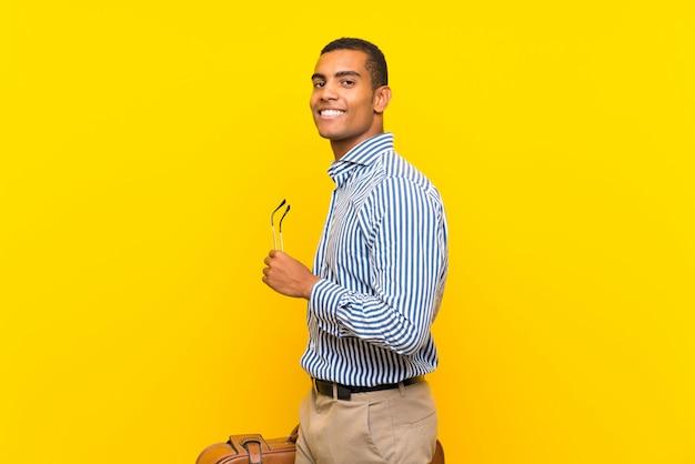 Hombre morena sosteniendo un maletín vintage sobre pared amarilla aislada