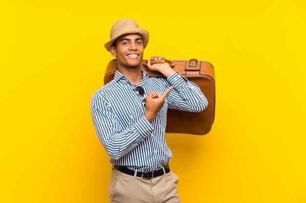 Hombre morena sosteniendo un maletín vintage sobre pared amarilla apuntando hacia un lado para presentar un producto