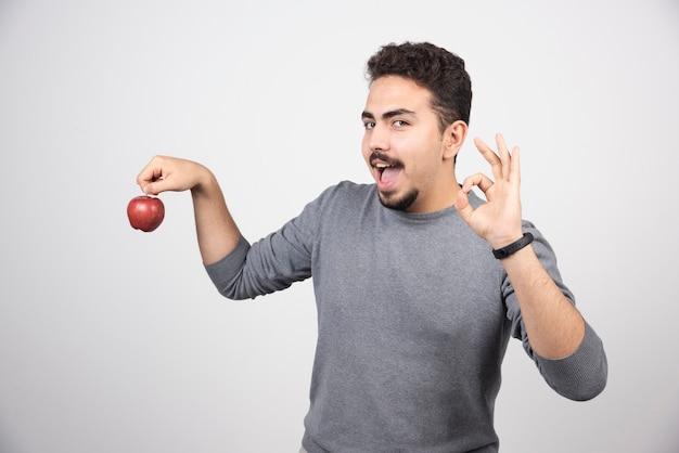 Hombre morena sosteniendo una manzana roja sobre un gris.