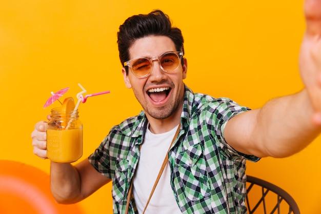 Hombre morena travieso con gafas de sol naranjas toma selfie, guiña un ojo y sostiene un cóctel dulce.