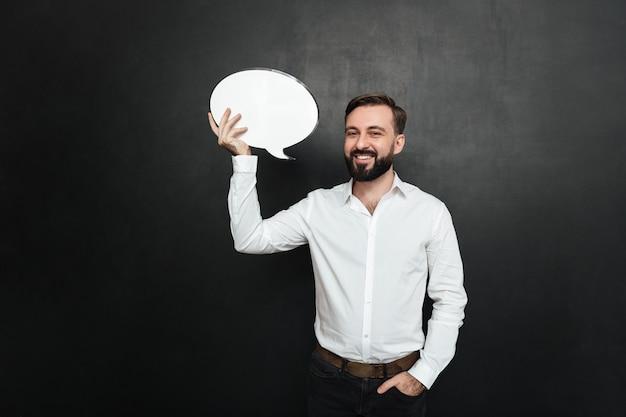 Hombre moreno atractivo que sostiene el bocadillo de diálogo en blanco y que mira la cámara sobre espacio gris oscuro de la copia de la pared