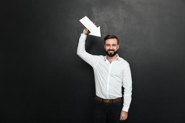 Hombre moreno atractivo que sostiene el puntero de flecha en blanco del discurso que dirige hacia él sobre espacio gris oscuro de la copia de la pared