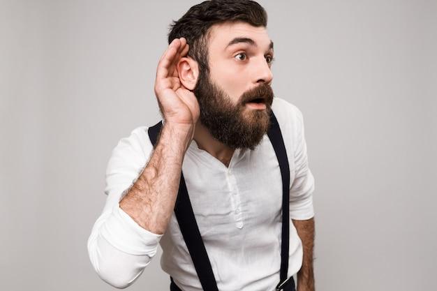 Hombre moreno hermoso joven que escucha a escondidas sobre blanco.