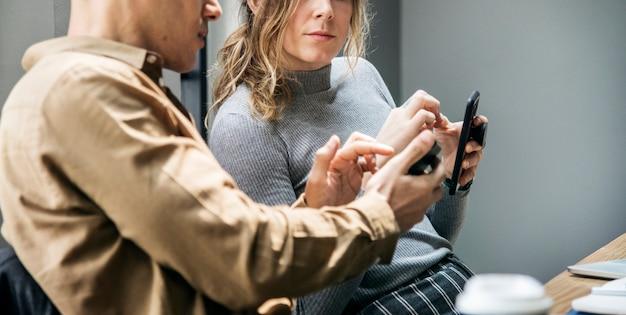 Hombre mostrando algo en un teléfono inteligente a una mujer