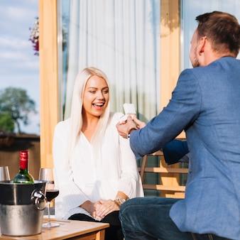 Hombre mostrando un anillo de compromiso a su novia asombrada en un restaurante