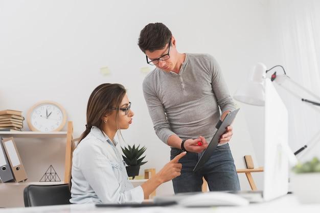 Hombre mostrando datos de un portapapeles a una mujer de negocios