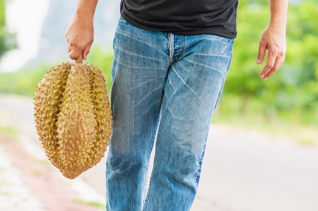 Hombre mostrando durian maduro felizmente