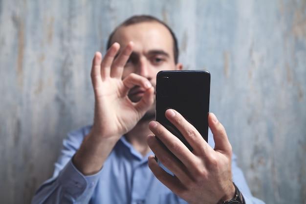 Hombre mostrando gesto ok y sosteniendo el teléfono inteligente.