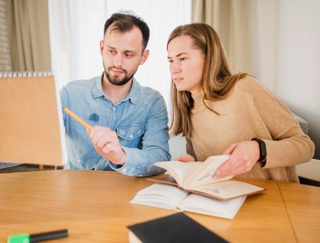 Hombre mostrando a mujer algo que escribió en el cuaderno