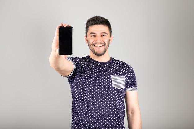 Hombre mostrando la pantalla en blanco de su teléfono