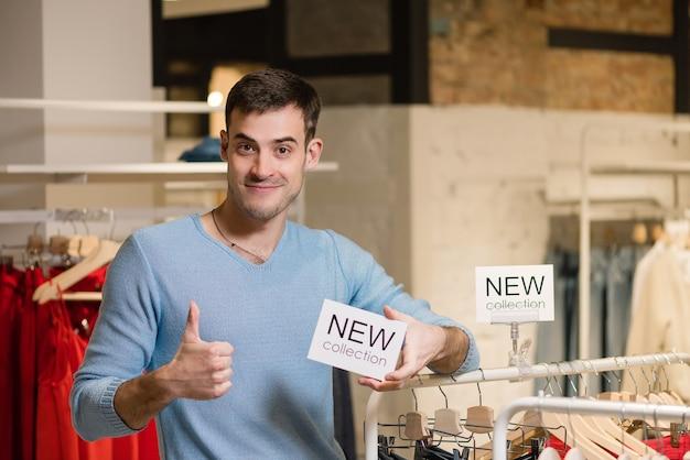 Hombre mostrando el pulgar hacia arriba y mantenga el cartel blanco con nuevas palabras de colección