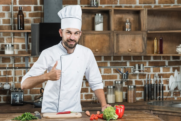 Hombre mostrando el pulgar en señal de pie detrás del mostrador de la cocina con verduras