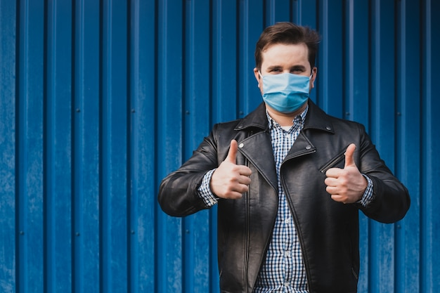 Hombre mostrando los pulgares hacia arriba y con máscara, coronavirus en cuarentena.