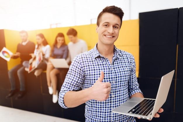 El hombre está mostrando los pulgares para arriba, sosteniendo el portátil en sus manos.