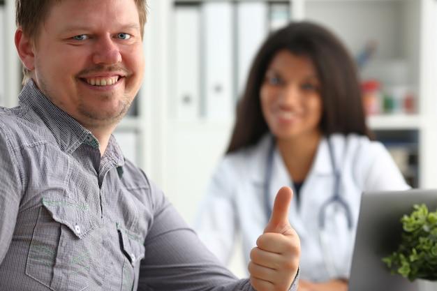 Hombre mostrando signo bien con el pulgar hacia arriba en el consultorio del médico