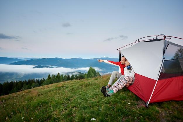 Hombre mostrando su mano en la distancia, sentado en una tienda de campaña cerca de la mujer desde la que se abre el paisaje de las poderosas montañas al amanecer. a lo lejos, en el cielo, la luna es visible