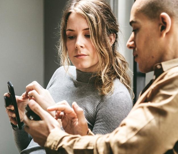 Hombre mostrando su teléfono inteligente a su amigo