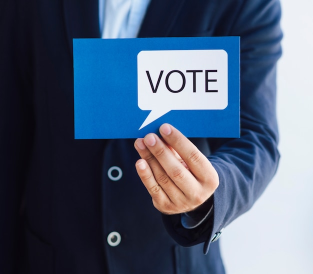 Hombre mostrando una tarjeta de votación con un bocadillo