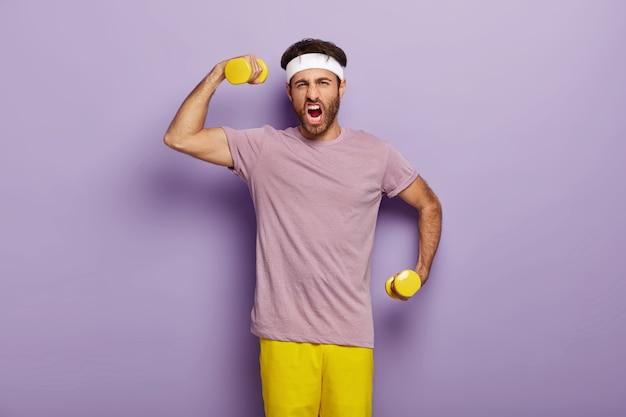 Hombre motivado entrena los músculos de las manos, levanta mancuernas, sacude los bíceps
