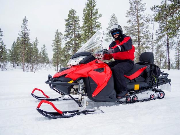 Un hombre en moto de nieve en la montaña de invierno