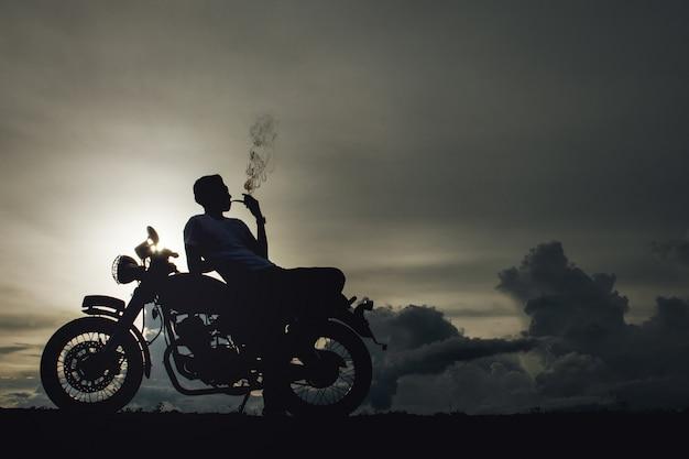 Hombre de motorista sentado fuma con su moto al lado del lago natural y hermoso.