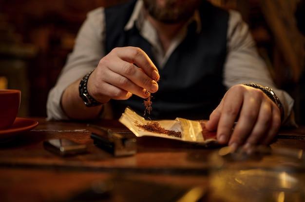 El hombre muele el tabaco, vista de cerca, mesa de madera. cultura de fumar, rico sabor específico. ocios de fumador masculino en office