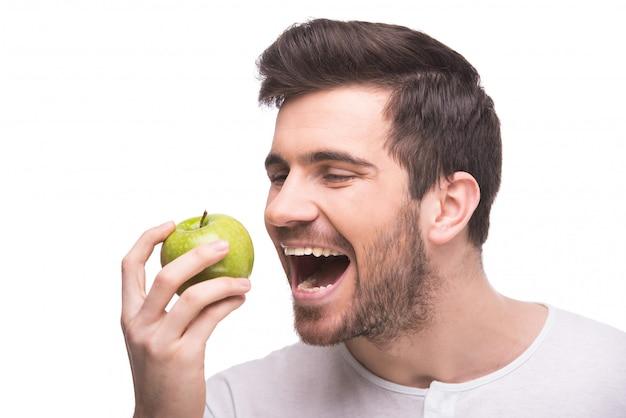 El hombre muerde una manzana verde