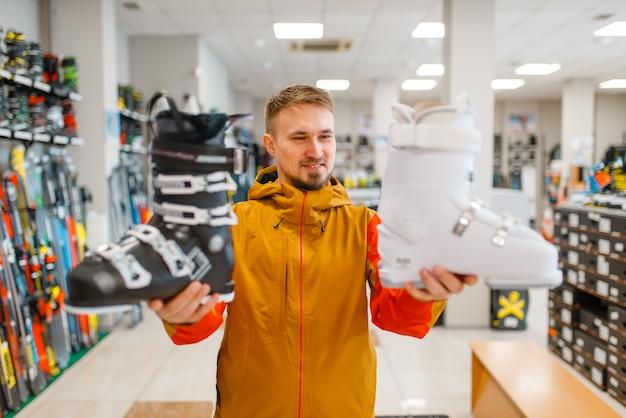 El hombre muestra botas de esquí o snowboard en tienda de deportes