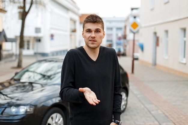 El hombre muestra una emoción de indignación cerca del coche en la calle