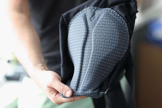 El hombre muestra el interior de la ropa deportiva para el asiento de la bicicleta eligiendo ropa deportiva de calidad para el concepto de ciclismo