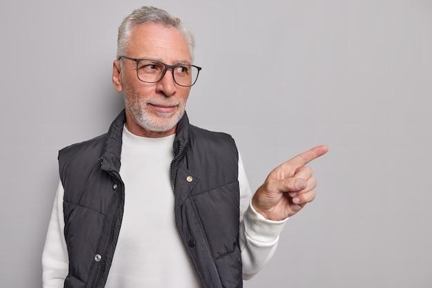 El hombre muestra una promoción presenta un nuevo producto con expresión segura de sí mismo usa gafas, un jersey informal y un chaleco muestra un espacio en blanco en gris